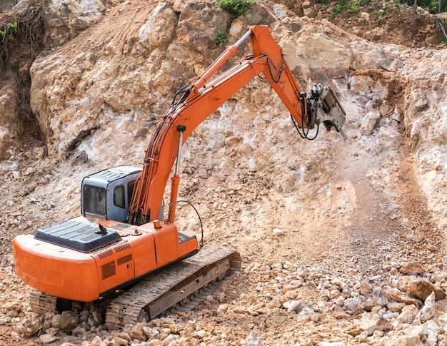 岩を砕く作業中の大型油圧削岩機。