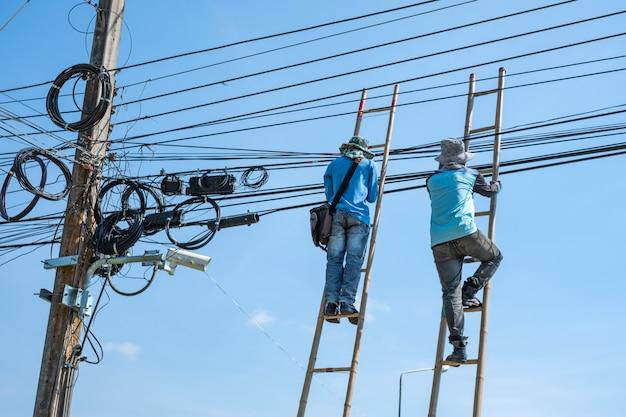 電気技師が電線を修理するために竹のはしごを登ります。