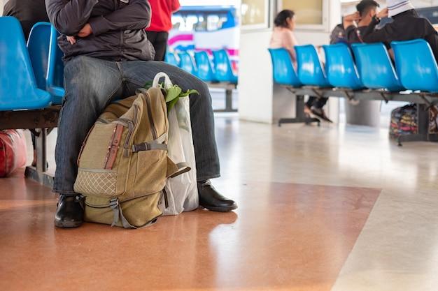 バッグを持つタイの旅行者は、タイのバンコクのバス停でターミナルでバスを待って座っています。