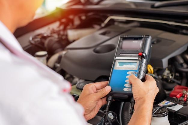 Техник проводит проверку автомобилей на ремонт автомобилей. с солнечным светом