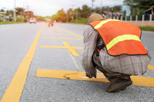 道路上の黄色の線を描く労働者。道路建設..太陽の光で
