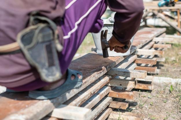 Плотник держит молоток и гвозди для строительных работ