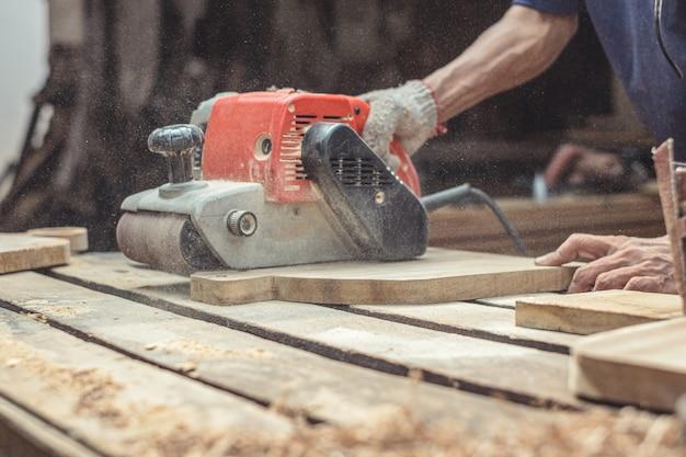 Карпентер шлифования древесины с ленточной шлифовальной машиной на мастерской в проекте деревянной разделочной доски или столярных работах по дереву