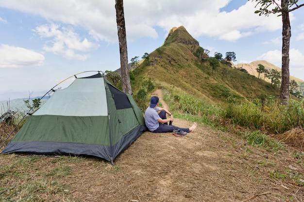 若い旅行者は、山の頂上で長時間ハイキングした後、テントの横に座っています。