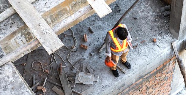 ストレス、憂鬱、そして絶望的なエンジニアまたは建築家の建設現場。彼は仕事に問題を抱えています。エンジニアリングの概念。上面図。