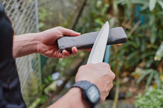 Рука держа нож и точильный камень, чтобы придать форму ножу. ручная заточка ножа.