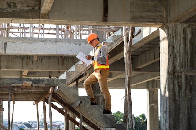 アジアの建築家またはエンジニアが見ているプロジェクトの青写真の論文を保持し、建設現場でヘルメットを着用します。彼は階段を歩いています。