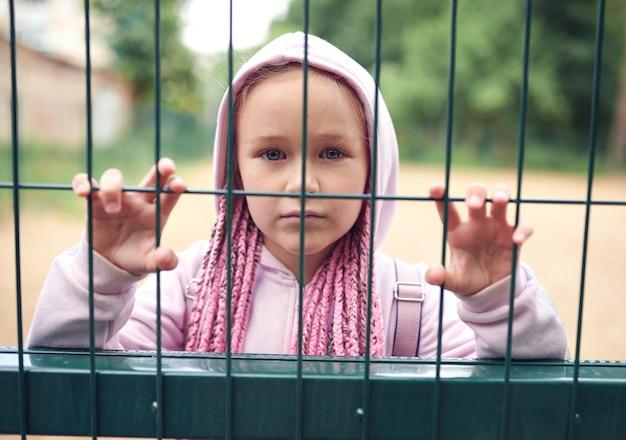 Портрет маленькой девочки с африканскими косичками, одетой в розовый костюм, грустный взгляд с другой стороны решетки.