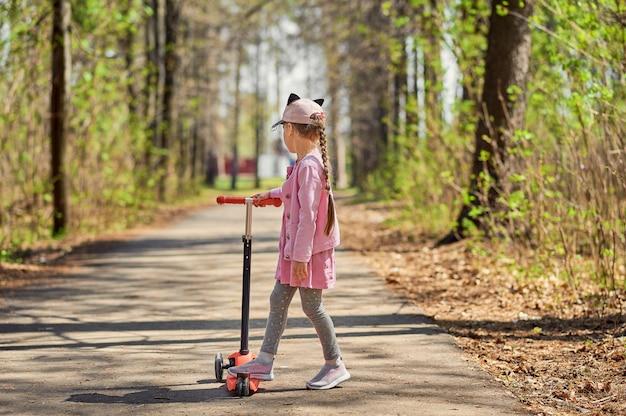 Маленькая девочка в кепке и розовой куртке погибла в заброшенном городском парке. маленькая девочка думает, куда идти.