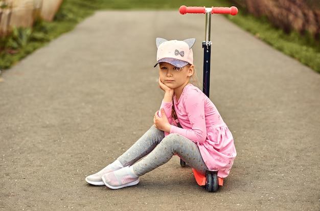 スクーターに座っている少女は何かを考えていました。赤いドレスと帽子の少女の眺め。