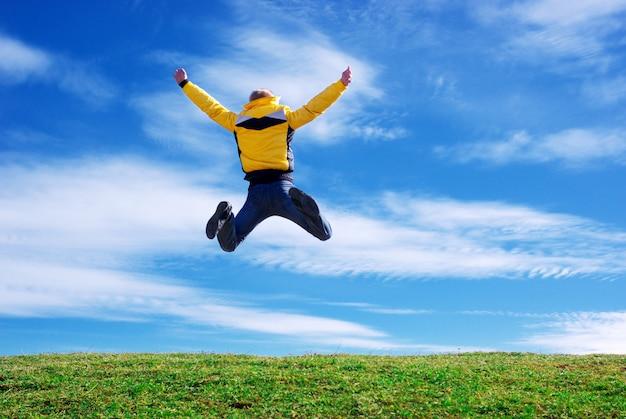 緑の牧草地の男ジャンプ