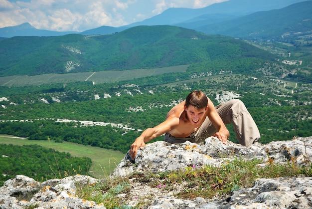 Человек карабкается на гору