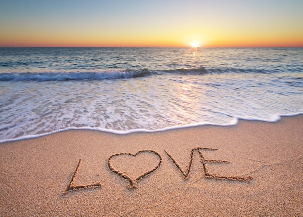 Любовное слово написано на песке на пляже