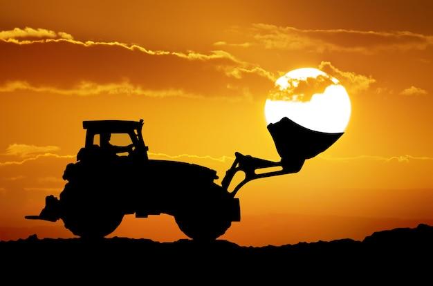 シャベルのバケツにトラクターと太陽。