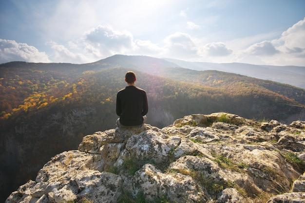 Человек сидит на скале горы.