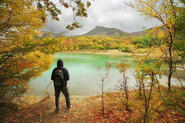 秋の池に一人で立っている男