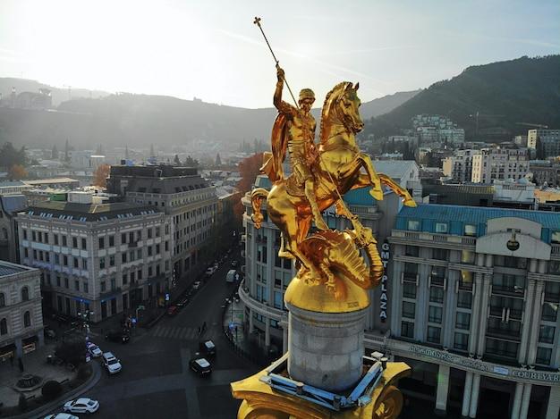 美しい空中ドローン写真。上から国ジョージア。首都トビリシ。自由広場と聖ジョージ黄金記念碑の肖像画を間近します。