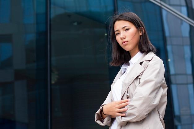 Серьезная, взволнованная, недовольная девочка, стоящая вне офисного рабочего места.