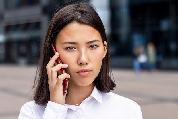 深刻なアジアビジネスの女性は携帯電話で話しています。