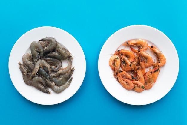 シーフード、調理済み、ゆで、または揚げたエビ、生の未調理のエビ、白プレートの青の車海老。上面図。健康的なタンパク質食品、ダイエット。比較。料理の前後。