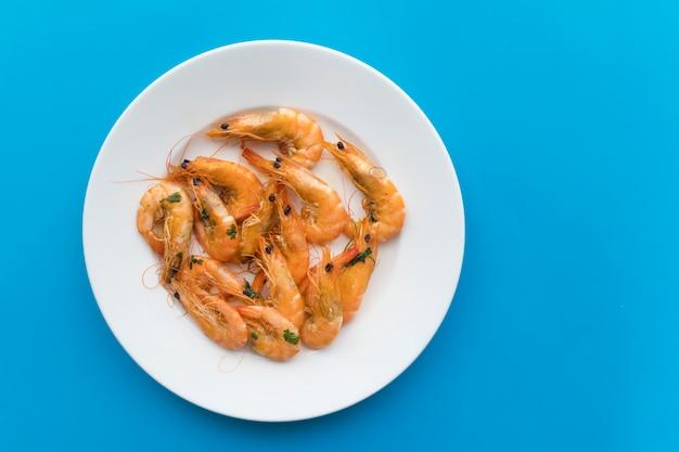 調理されたエビ、揚げられたまたはゆでられた魚介類、緑のハーブが付いている王の車海老、白い皿の上のスパイス。上面図。健康的なタンパク質食品、ダイエット。
