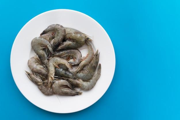 未調理の生の新鮮な魚介類、白いプレートにキングタイガーグレー海老。上面図。健康的なタンパク質食品、ダイエット。