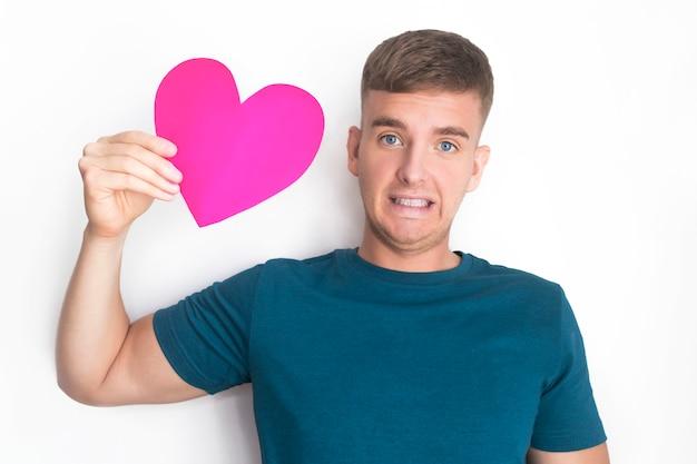 Удивленный красивый парень держит, получил сердечную открытку на день святого валентина. молодой позабавил шокирован красивый мужчина с розовым красным валентина улыбается. блондинка европейский мальчик