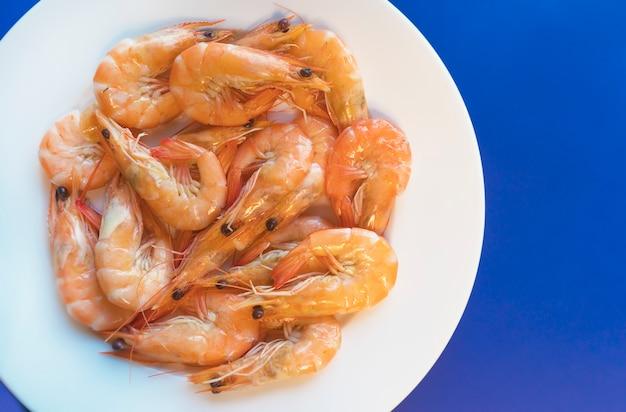 調理されたエビ、揚げられたまたはゆでられた魚介類、緑のハーブが付いている王の車海老、白い皿の上のスパイス。上面図。健康食品。減量のための炭水化物を含まないケトプロテインダイエット