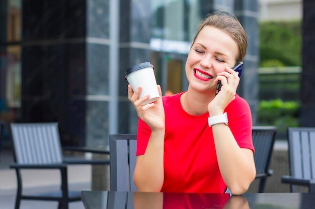 Счастливая позитивная девушка, молодая жизнерадостная женщина в красном, улыбается, отдыхает, наслаждается беседой, беседует, разговаривает по мобильному телефону, кофе с собой, смеется, сидит в кафе на террасе, хорошо проводит время