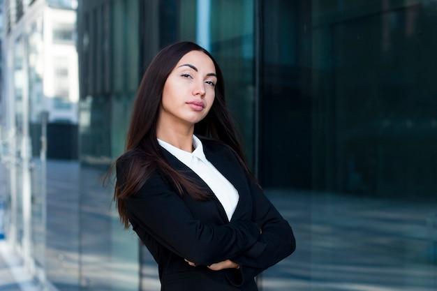 オフィスモダンな建物、ビジネスセンターの近くに屋外に立っているセクシーな自信を持って成功した実業家。彼女の手で白人の熱い東部女性、腕を組んで