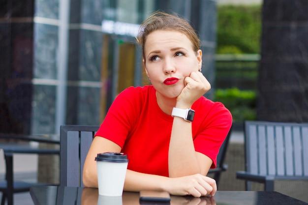 思慮深い孤独な物思いに沈んだ退屈少女、スマートフォン、コーヒーカップ、思考、夢のテラスのカフェに座っている若い美しい女性。日付を待っている手で赤い小道具のあごの女性