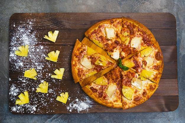 甘いパイナップルスライス、チキン、ソース、チーズが入ったおいしいおいしいホットハワイアンエキゾチックスライスピザ。トップビューの組成、イタリアの国民食。ダーク、ブラウン、グレーの木製、ローキー。