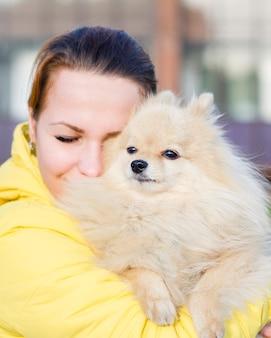 垂直方向の写真、目で彼女のポメラニアンスピッツ犬を抱いて幸せな若い女性の肖像画は、歩行中に閉じた。女の子の所有者は屋外で彼女のペットのふわふわかわいい子犬を愛しています。優しさ、動物の世話の概念。