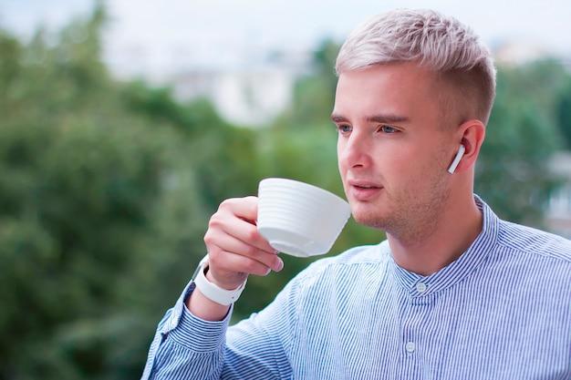 カップから飲み物、お茶、コーヒーを飲む物思いにふける思慮深い男。屋外のワイヤレスイヤホンで音楽を聴くシャツのガジェットを持つ若者。