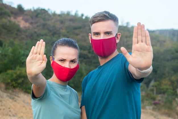 Молодая милая пара, девушка женщина и парень, мужчина в защитной медицинской маске на лице на открытом воздухе, показать ладонь, рука, не остановить знак. загрязнение воздуха, вирус, китайская концепция пандемического коронавируса