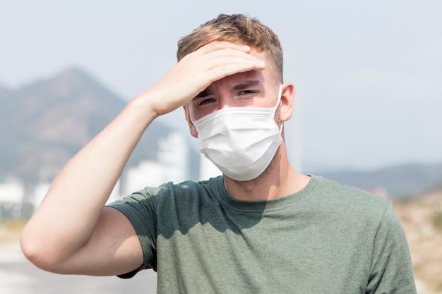 ガイ、高熱に苦しんでいる顔の保護滅菌医療マスクで病気の若いヨーロッパ人男性。コロナウイルスのコンセプト