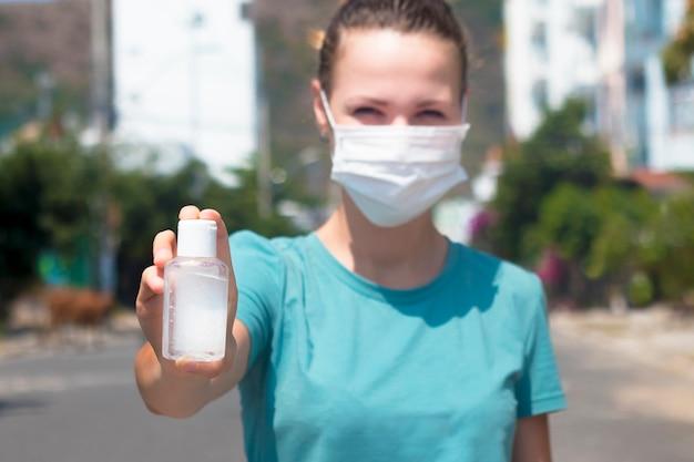 Молодая женщина дезинфицирует руки, девушка в защитной медицинской маске на лице показать бутылку с дезинфицирующим средством