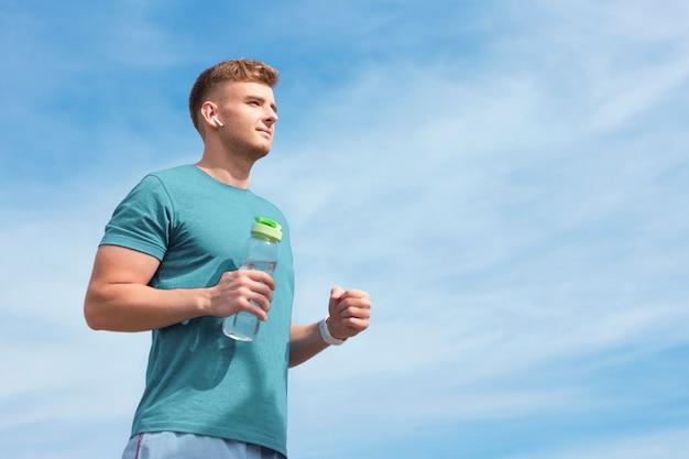 水のボトルを持つ運動スリムハンサムな男ランナーの若い美しい男は、ジョギングランニング中にワイヤレスイヤホンで音楽を聴きます。コピースペース。アクティブな健康的なライフスタイルのコンセプト。青空