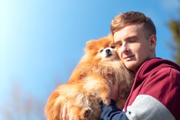 Красивый парень, молодой симпатичный хозяин с собакой померанского шпица, маленький милый сладкий щенок на руках. люди любят животных, животных концепции. мальчик держи, обними свою прекрасную собаку. копирование пространства на фоне голубого неба