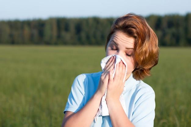 屋外の紙ハンカチで鼻水、ティッシュで彼女の鼻を吹く若い女性。病気の少女は、夏の畑で目を閉じてくしゃみをします。自然な背景。気分が悪く、病気、悪い、苦しんでいます。アレルギー。