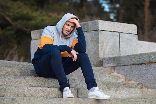 不幸な悲しい動揺落ち込んで泣いている男、フードの階段に座っている孤独な欲求不満の絶望的な若者、機嫌が悪い、問題、感情的な痛みのために苦しんでいます。失恋、失敗のコンセプト。