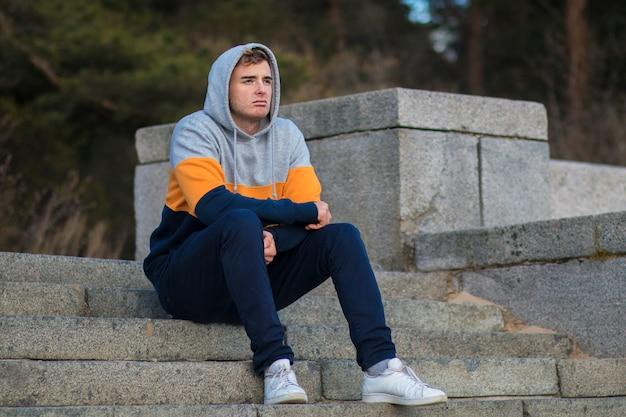 悲しい動揺して落ち込んでいる男、フードの階段に座っている孤独な欲求不満の若者、機嫌が悪いために苦しんでいる、将来の問題について考えている、遠くを見ている。失恋、失敗のコンセプト。