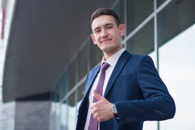 スーツとネクタイの親指を現して、承認のシールのような幸せな自信を持って陽気なビジネスマン。成功した男の屋外オフィスビル、ビジネスセンターの肖像画。
