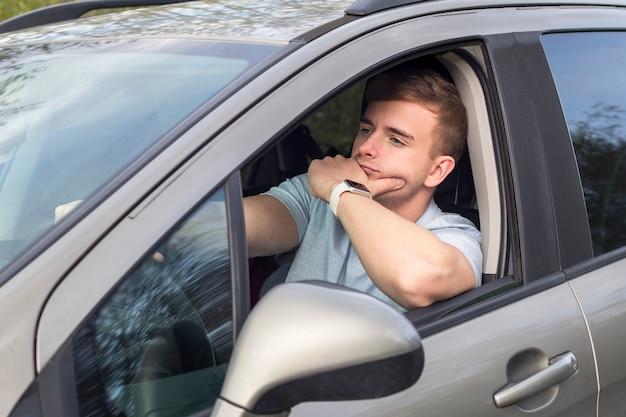 退屈な男、車を運転している若いハンサムな絶望的な男、過ごす、時間を浪費する、退屈な交通渋滞で立ち往生。長い道のりで、道路上の問題のために疲れたドライバーが苦しんでいます。否定的な表情