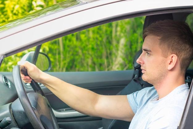 若いハンサムな集中男、緩んだドライバー、深刻な男が車を運転、自動車のホイールを握り、ロードトリップを楽しんでいます。側面図。