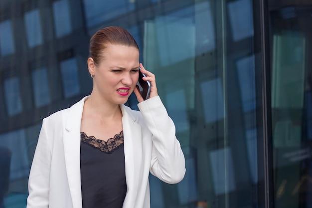 怒って、イライラして、イライラして実業家の話、叫んで、屋外の携帯電話で宣誓します。女性の上司が叫び、スマートフォンで従業員に叫んでいます。不快な会話、接続不良、聞き取りにくい