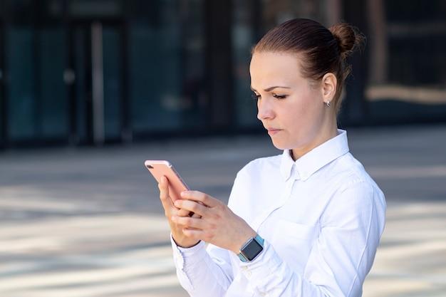 深刻な若い美しいビジネス女性、集中した女の子が彼女のスマート携帯電話を見てください。