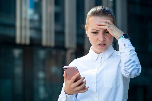 Грустная разочарованная измученная деловая женщина, молодая девушка смотрит на свой мобильный смартфон