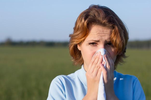 Больная страдающая молодая женщина, чихающая и сморкающаяся, держа в руках носовой платок в летнем поле. девушка с симптомом аллергии, гриппа или простуды.