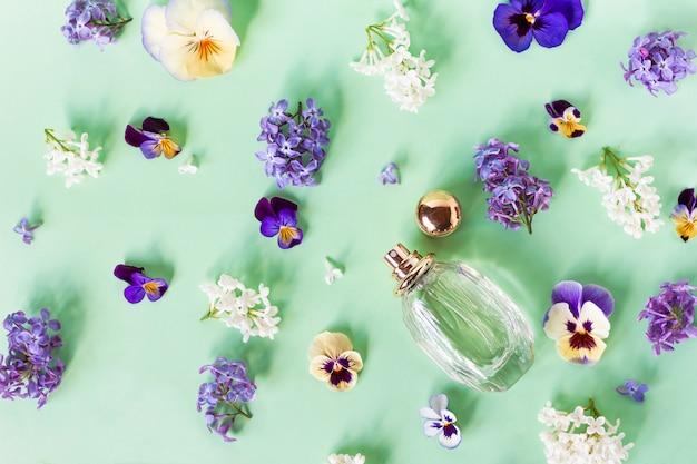 Натюрморт, композиция, набор из свежих красивых красочных цветов, аромат и флакон с женскими духами. фиалки и сирень. вид сверху. квартира лежала.
